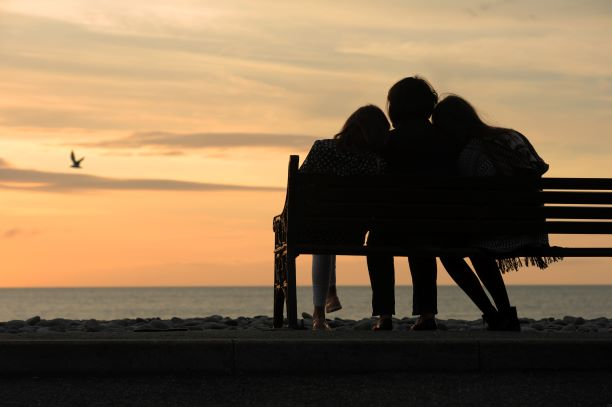 Three friends sit on a bench facing the sea. It is sunset and the people are in shadow and facing away from the camera.