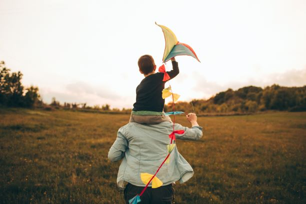 a small child sits on the shoulders of an adult. They are outside in an open field. The image is taken from behind them so their backs are towards the camera. The child is holding a brightly coloured kite.