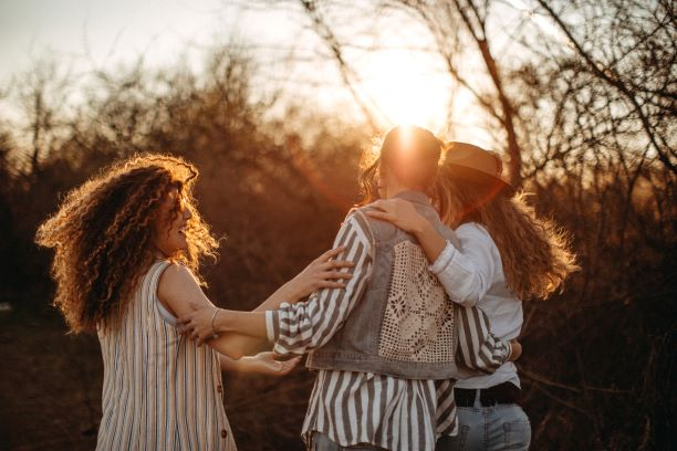 a group of three friends laughing together. They are facing away from the camera. The setting sun is shining just above their heads