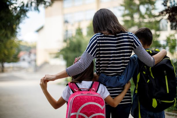 Image of a woman walking with her two young children. They have their arms around each other and are walking away from the camera so we see a back view.