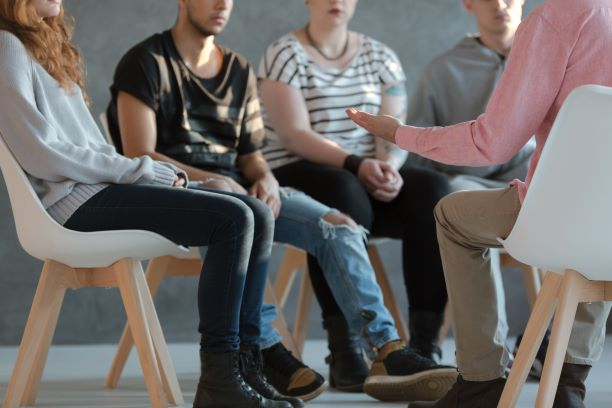a group of young people sat in a circle having a discussion. You can not see their faces